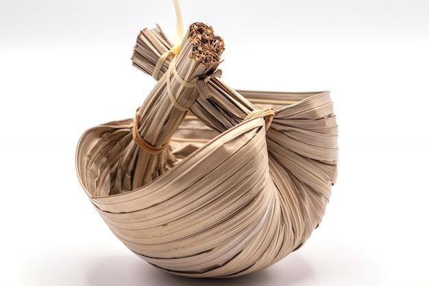 Um recipiente feito com licença de palma seca de nipa ou isolado de licença de palmeira de mangue em branco.