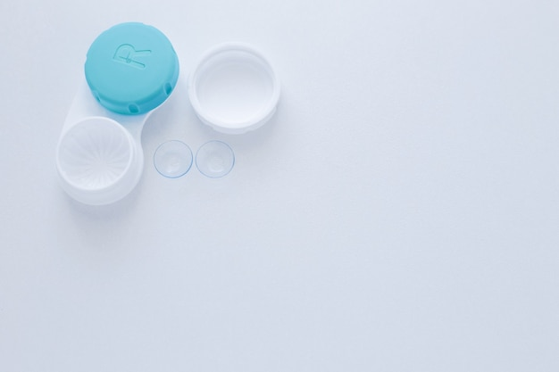 Um recipiente para lentes e duas lentes de contato estão na lateral em um fundo branco com espaço para t ...
