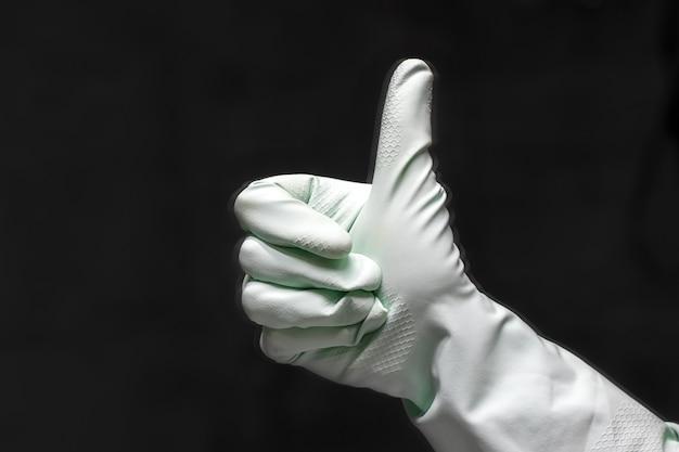 Um reflexo de mão em uma luva de borracha verde menta mostra os polegares em um quarto escuro. foco seletivo. vista de perto