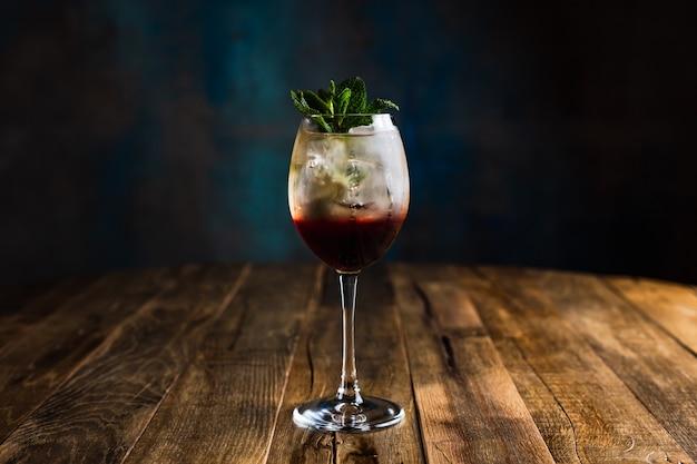 Um refrescante coquetel gelado em camadas em um copo de vinho decorado com hortelã
