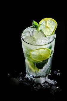 Um refrescante coquetel mojito de verão. bebida alcoólica com gelo e limão em um fundo preto.