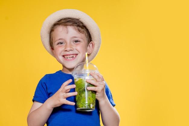 Um refresco de verão, uma bebida gelada, um menino com um copo de plástico de limonada fresca