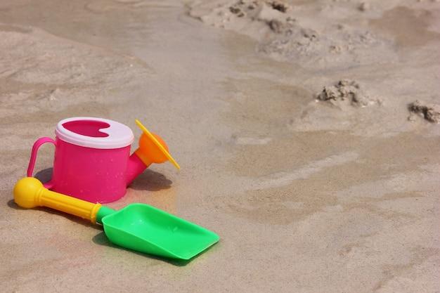 Um regador de brinquedo e uma pá de brinquedo estão localizados na areia da costa do mar.