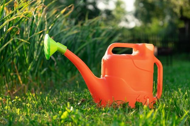 Um regador de plástico laranja fica na grama verde no jardim de verão