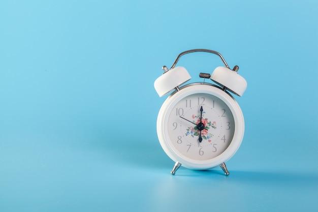 Um relógio branco em uma parede azul