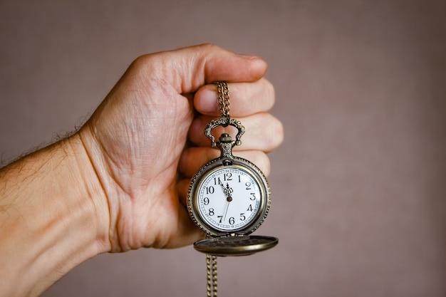 Um relógio de bolso nas mãos de um homem