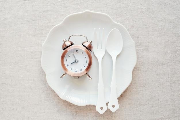 Um relógio na placa, conceito de dieta de jejum intermitente