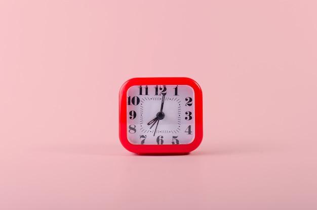 Um relógio vermelho em rosa