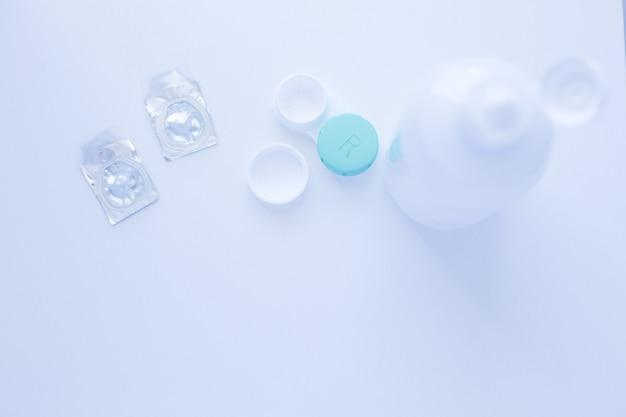 Um removedor de lentes, um recipiente de armazenamento de lentes e duas lentes de contato ficam em cima da foto em um fundo branco ...