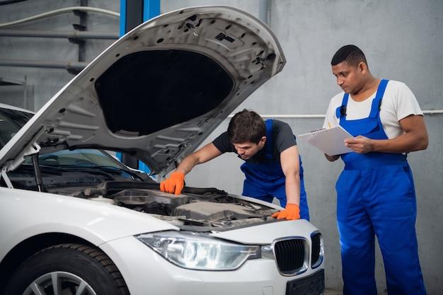 Um reparador de uniforme azul examina o motor de um carro quebrado. seu parceiro faz anotações