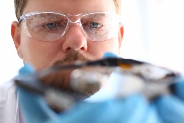 Um reparador masculino de luvas azuis está segurando