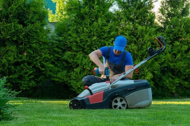 Um reparador profissional conserta um cortador de grama e um homem conserta um cortador de grama em seu quintal