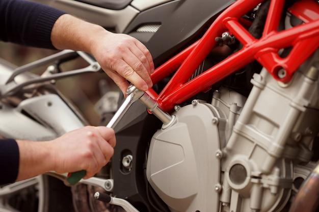 Um reparador trabalha com motocicleta no serviço