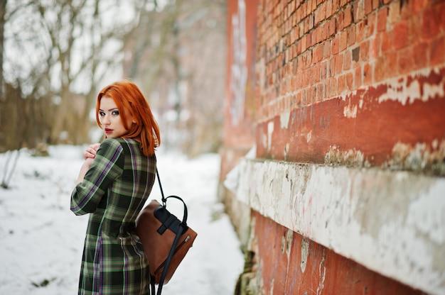 Um retrato ao ar livre de uma jovem mulher bonita com cabelo vermelho, vestido xadrez com mochilas femininos em pé na parede de tijolo em dia de inverno.