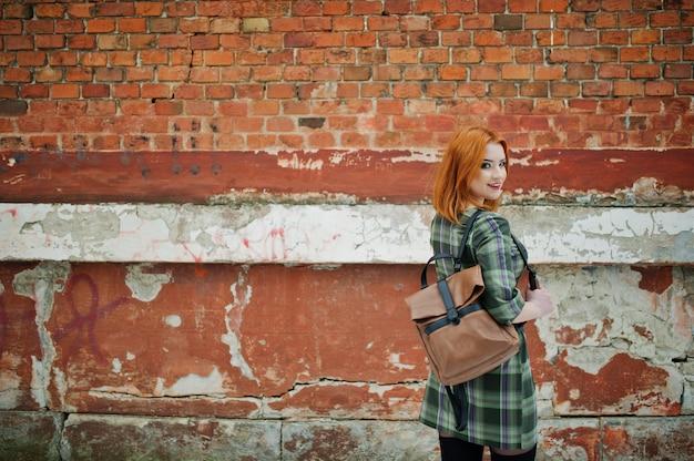 Um retrato ao ar livre de uma jovem mulher bonita com cabelo vermelho, vestido xadrez com mochilas femininos em pé na parede de tijolo.