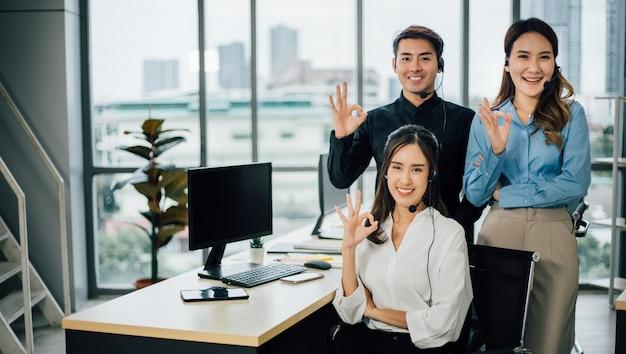 Um retrato da equipe de suporte ao cliente asiático com fone de ouvido, mostrando um gesto ok.