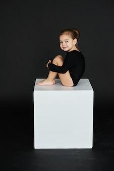 Um retrato da menina bonita vestiu-se em calças justas pretas em um cubo branco contra o fundo escuro.