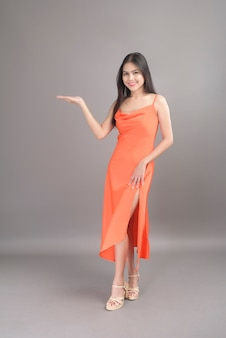 Um retrato da moda de uma linda mulher usando um vestido laranja isolado sobre o estúdio de fundo cinza