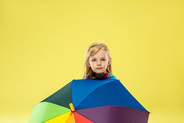Um retrato de corpo inteiro de uma garota elegante e brilhante com guarda-chuva arco-íris