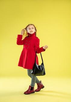 Um retrato de corpo inteiro de uma garota elegante e brilhante com uma capa de chuva vermelha e uma bolsa preta posando na parede amarela do estúdio
