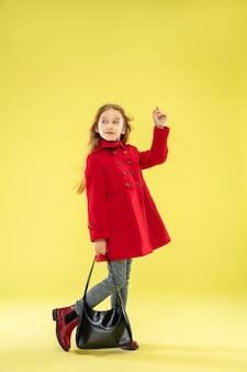 Um retrato de corpo inteiro de uma garota elegante e brilhante em uma capa de chuva vermelha segurando uma bolsa preta na parede amarela do estúdio