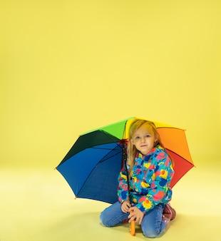 Um retrato de corpo inteiro de uma garota elegante e brilhante em uma capa de chuva