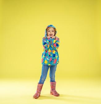 Um retrato de corpo inteiro de uma garota na moda brilhante em uma capa de chuva segurando um guarda-chuva das cores do arco-íris em amarelo.