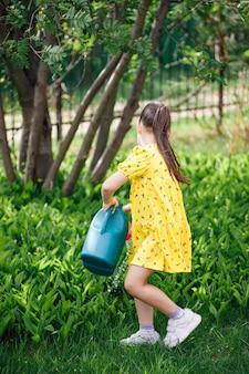 Um retrato de corpo inteiro de uma menina em um vestido amarelo regando lírios do vale de uma rega azul ...