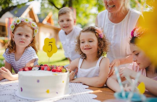 Um retrato de crianças com bolo em pé ao redor da mesa na festa de aniversário no jardim no verão.