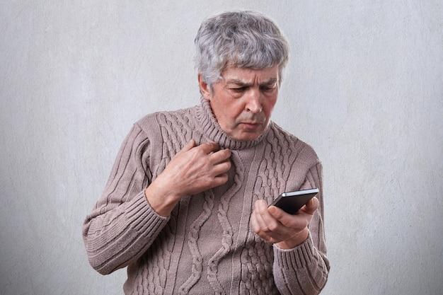 Um retrato de homem idoso com cabelos grisalhos, tendo expressão chocada enquanto olha para seu smartphone lendo a mensagem