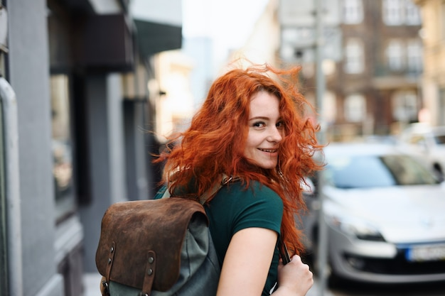 Um retrato de jovem com mochila, caminhando ao ar livre na cidade, olhando para a câmera.