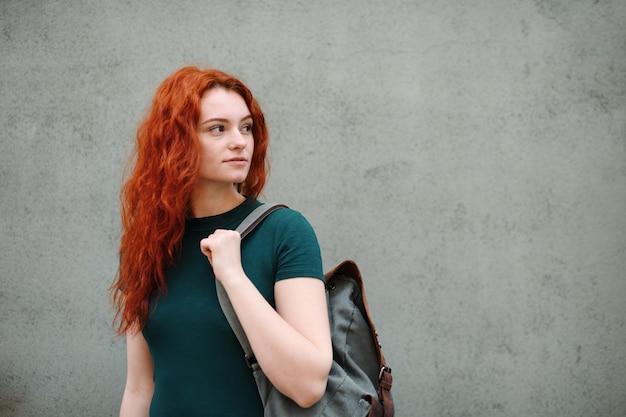 Um retrato de jovem com mochila em pé ao ar livre contra um fundo cinza. copie o espaço.
