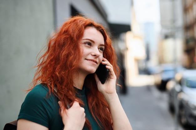 Um retrato de jovem com mochila em pé ao ar livre na rua da cidade, usando o smartphone.