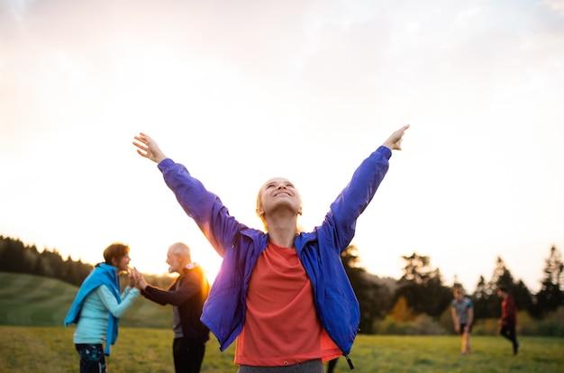 Um retrato de jovem com um grande grupo de pessoas fazendo exercícios na natureza, descansando.