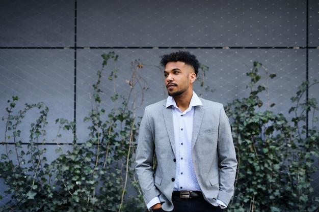 Um retrato de jovem estudante em pé ao ar livre na cidade, com as mãos nos bolsos.