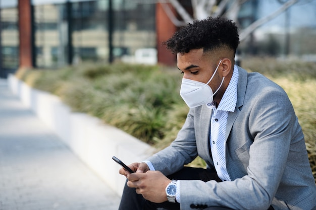 Um retrato de jovem sentado ao ar livre na cidade, usando o smartphone. conceito de coronavírus.