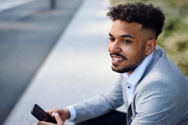 Um retrato de jovem sentado ao ar livre na cidade, usando o smartphone.