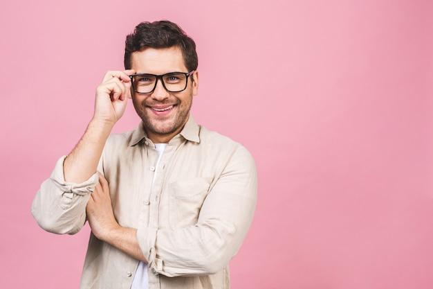 Um retrato de jovem sorridente homem de negócios bonito na camisa casual isolada tocando seus óculos.