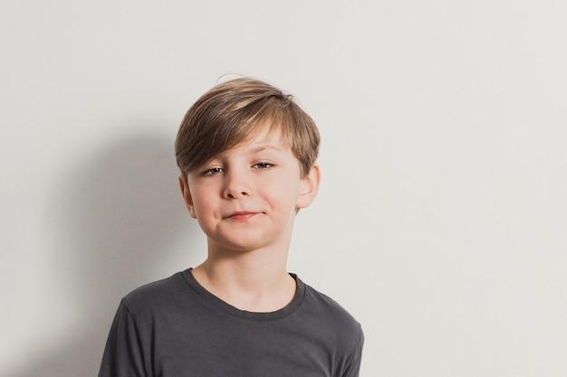 Um retrato de menino bonito, fazendo caretas, olhar esnobe