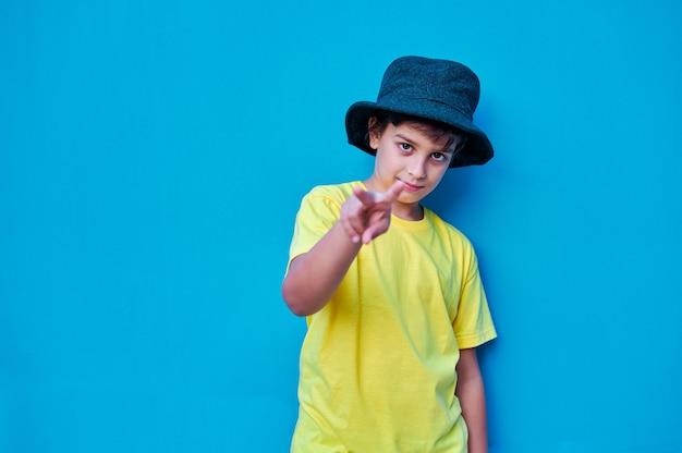 Um retrato de menino desafiador em t-shirt amarela e chapéu fazendo