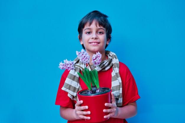 Um retrato de menino em t-shirt vermelha e lenço listrado segurando uma planta de jacinto. na parede azul. copie o espaço