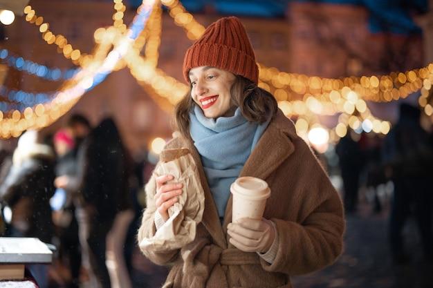 Um retrato de mulher sorridente, sonhando perto da loja e segurando um café com comida para viagem no mercado de natal, andando no centro da cidade durante as férias. foto de alta qualidade