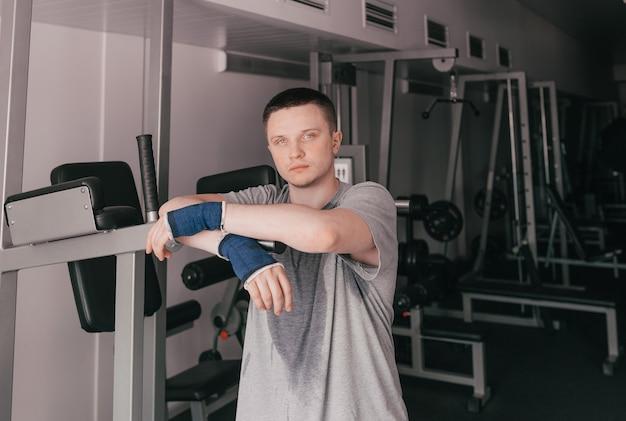 Um retrato de um atleta cansado com uma camiseta molhada está perto do simulador. descanse depois de um treino intenso