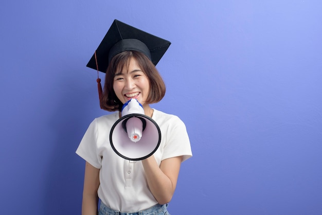 Um retrato de um estudante asiático graduado segurando um megafone isolado no estúdio de fundo roxo