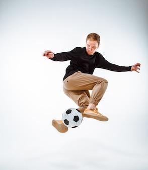 Um retrato de um fã com a bola no fundo cinzento do estúdio. freestile