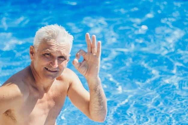 Um retrato de um homem adulto com cabelos grisalhos na água mostra o sinal de que tudo está bem. curtimento, recreação, turismo, linguagem gestual