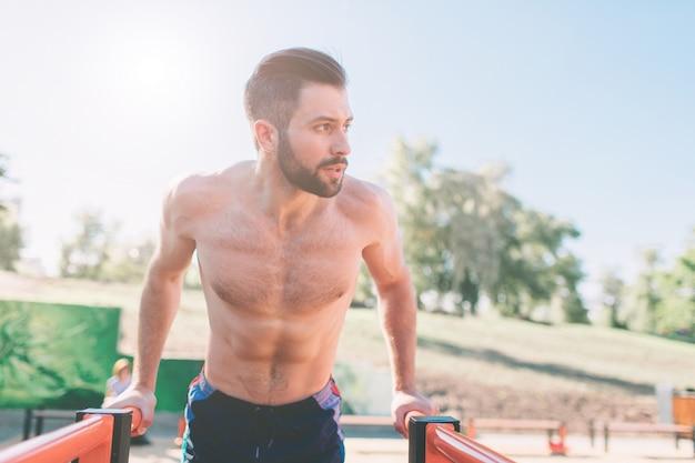 Um retrato de um homem barbudo musculoso focado em roupas de ginástica preta fazendo mergulhos em barras paralelas. equipa a aptidão com céu azul ao fundo e espaço aberto ao seu redor. esportes e crossfit.