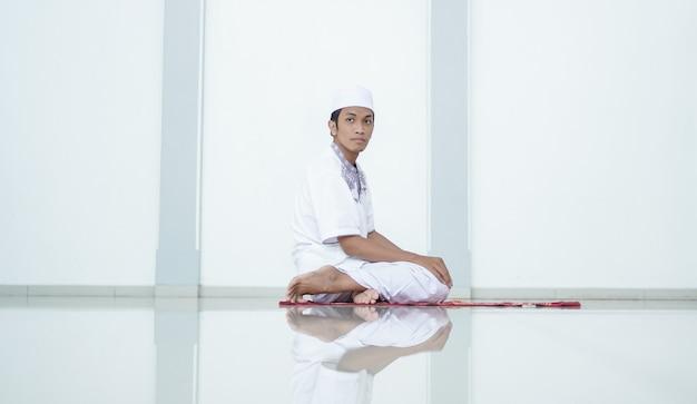 Um retrato de um homem muçulmano asiático orando na mesquita, o nome da oração é sholat, respeitando o fim do sholat