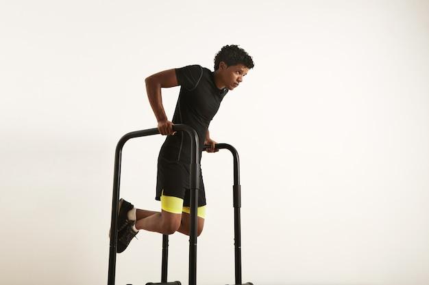 Um retrato de um jovem afro-americano concentrado e musculoso em roupas de ginástica pretas, fazendo mergulhos em barras paralelas em branco