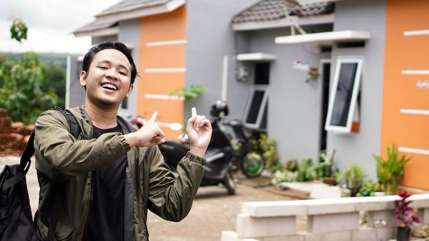 Um retrato de um jovem em frente à sua nova casa